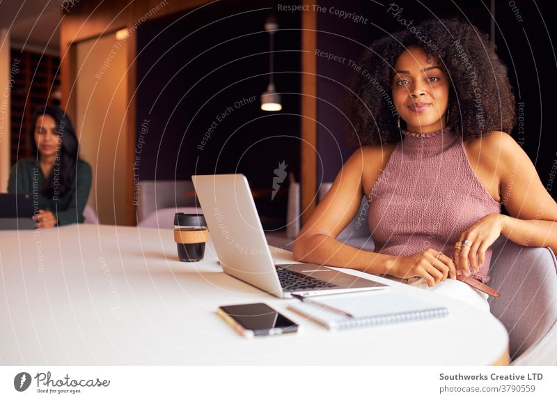 Portrait Of Businesswoman With Laptop At Socially Distanced Meeting In Office During Health Pandemic business businesswomen meeting social distancing