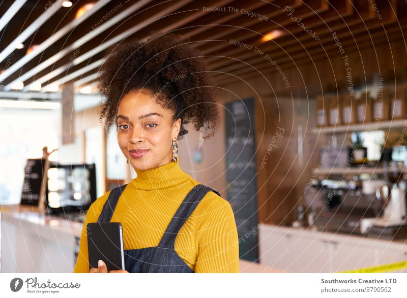 Portrait Of Female Business Owner Of Coffee Shop In Mask Using Digital Tablet During Health Pandemic business small business owner coffee shop cafe