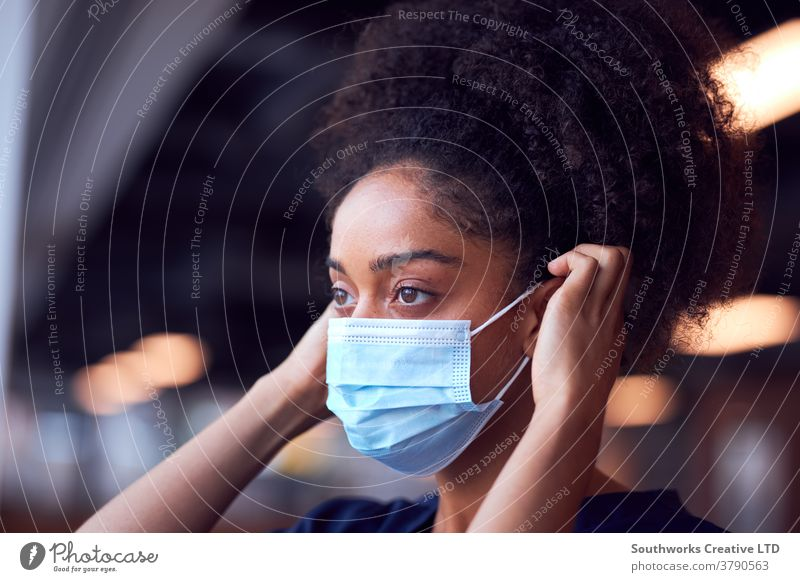 Female Doctor In Scrubs Putting On Face Mask Under Pressure In Busy Hospital During Health Pandemic doctor nurse scrubs key worker female woman putting on
