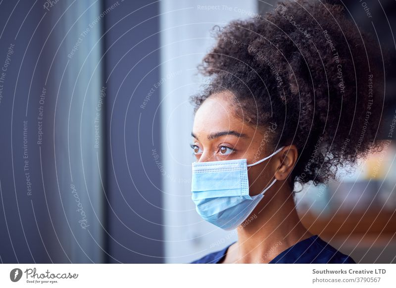 Female Doctor In Face Mask Wearing Scrubs Under Pressure In Busy Hospital During Health Pandemic doctor nurse scrubs key worker female woman wearing face mask