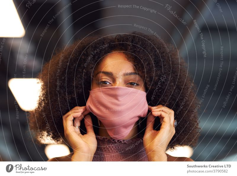 Portrait Of Businesswoman Putting On Face Mask In Modern Open Plan Office During Covid-19 Pandemic business businesswoman face mask face covering ppe putting on