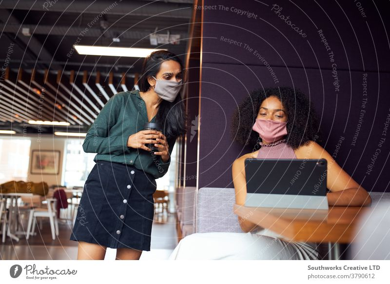 Businesswomen Wearing Masks Having Socially Distanced Meeting In Office During Health Pandemic business businesswomen meeting face mask face covering ppe