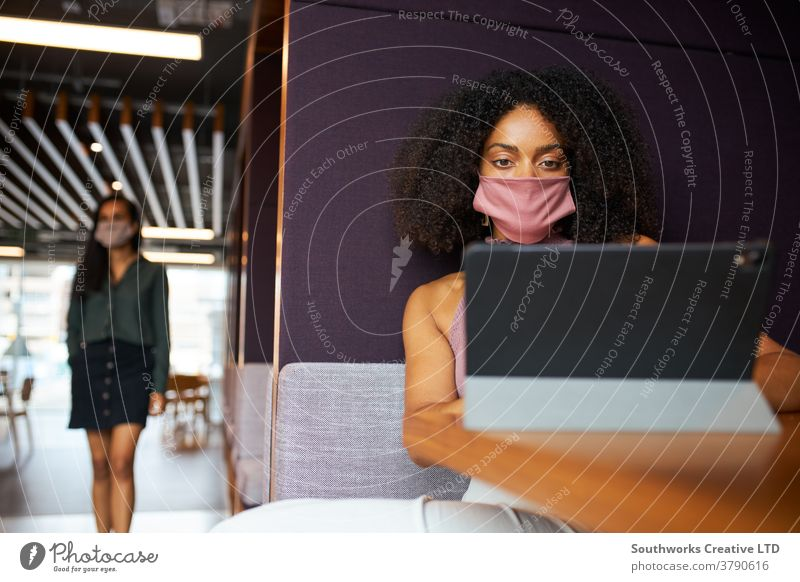 Businesswoman Wearing Mask Working In Socially Distanced Cubicle In Office During Health Pandemic business businesswoman face mask face covering ppe office