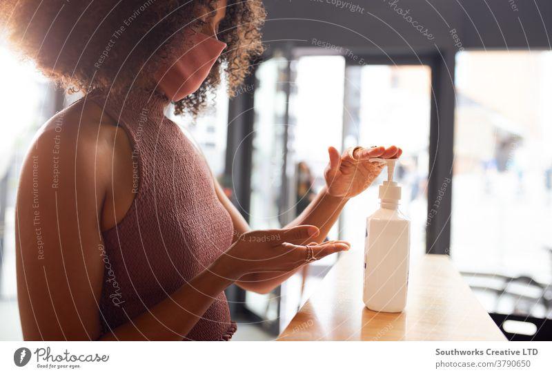 Businesswoman using hand sanitizer before entering office female employee gel sanitiser dispenser business businesswoman 20's millennial twenties young adult
