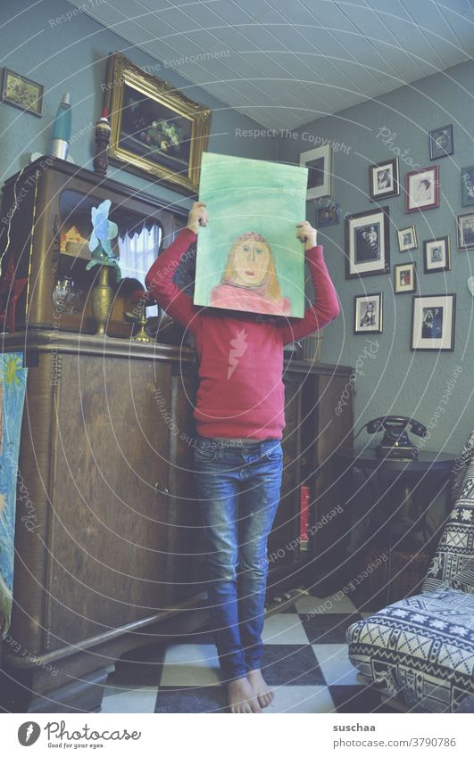 child with painted self-portrait in front of the head Child Girl Self portrait artist Painted Drawing Head Face Paper Work of art Flat (apartment) dwell
