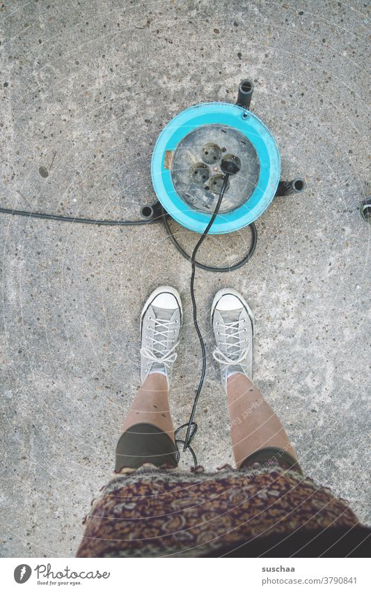 cable drum with power connection on asphalt, beside it the legs of a female person power supply portable Power plug power cable Connection Socket Cable
