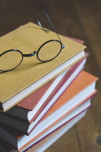 stack of books with glasses on top Book pile of books Eyeglasses tranquillity relaxation Reading Time Autumn Winter cold season autumn colours time change