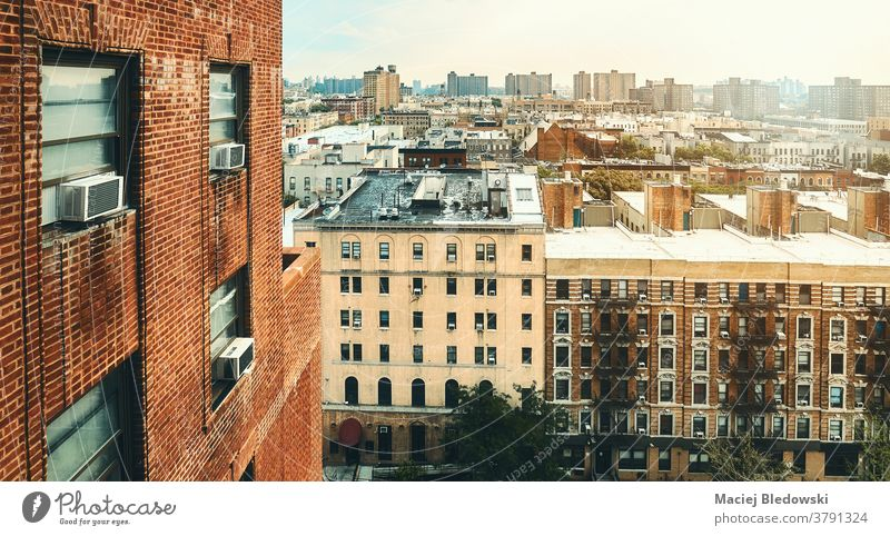 Harlem neighborhood cityscape at sunset, New York City, USA. building house brick residential skyline photo air conditioner window urban wall street town