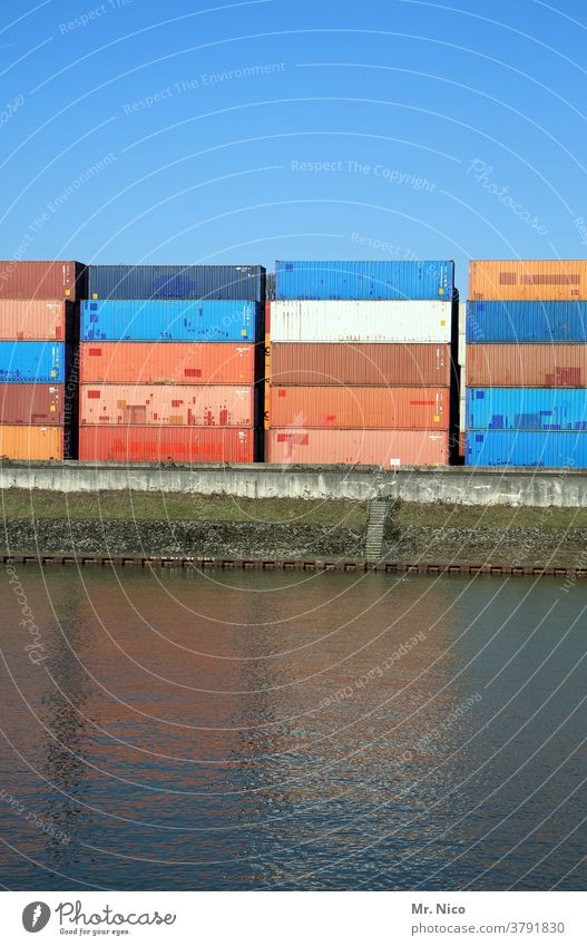 Stacked containers in the port Container Harbour Container terminal Logistics Port City Container cargo Trade Navigation Economy Water Blue sky pile Reflection