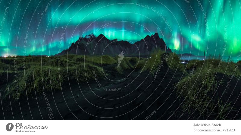 Northern lights over mountains at night northern aurora borealis scenic illuminate highland sky iceland color terrain dark rocky scenery picturesque environment