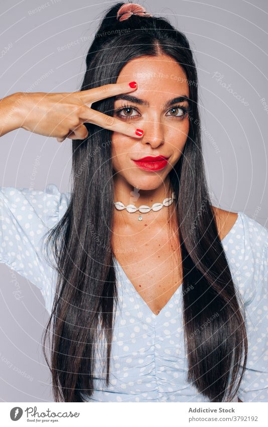Trendy young brunette with bright makeup and manicure woman style beauty fashion red lips two fingers confident ethnic female long hair colorful cosmetic