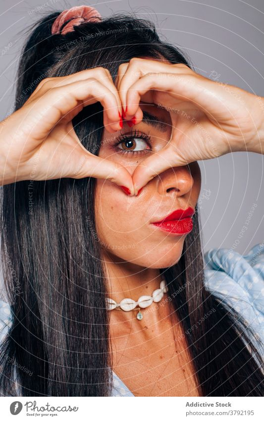 Stylish ethnic woman with heart shaped gesture sign style love friendship brunette finger romantic young millennial female red lips bright symbol human face