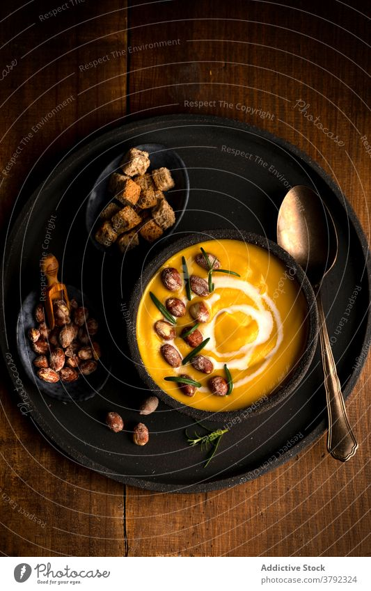 Appetizing pumpkin cream soup in bowl on table dish serve lunch bread crouton healthy food vegetarian wooden meal delicious organic gourmet vegetable cuisine