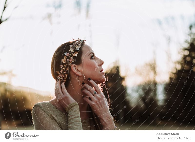 Charming woman in copper wreath touching neck gently in nature charming touch neck sensual pleasant serene gentle tender sensitive trendy gorgeous grace