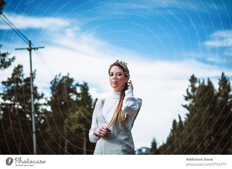Positive woman touching hair against evergreen forest calm positive touch hair charming gentle nature gorgeous romantic tender tranquil serene elegant trendy