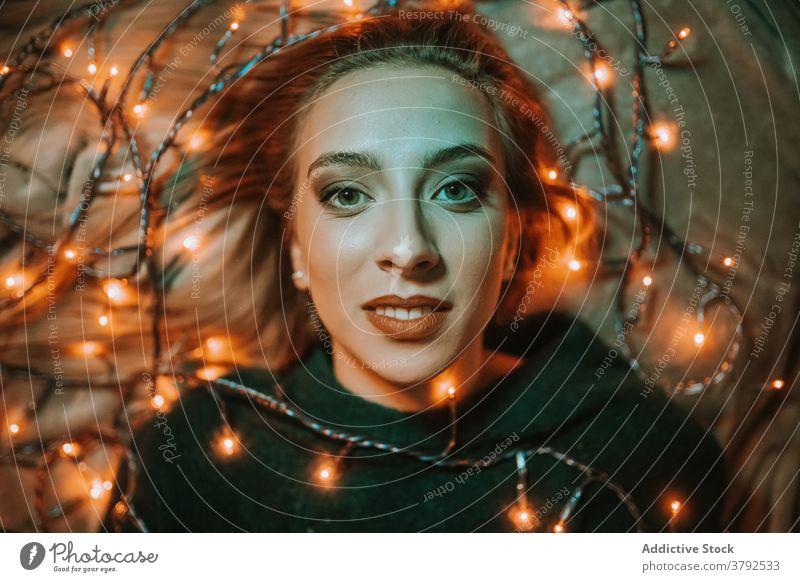 Stylish woman lying on bed with glowing garland luminous illuminate dreamy christmas smile light shiny style makeup festive xmas dark night human face cozy