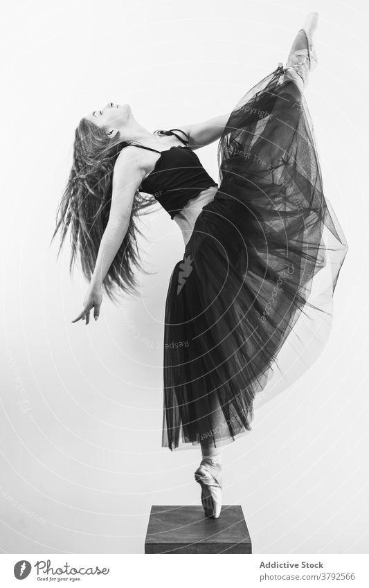 Slender ballerina in ballet pose on stool position tiptoe pointe shoe balance grace slim female professional dance perform dancer classic skill choreography