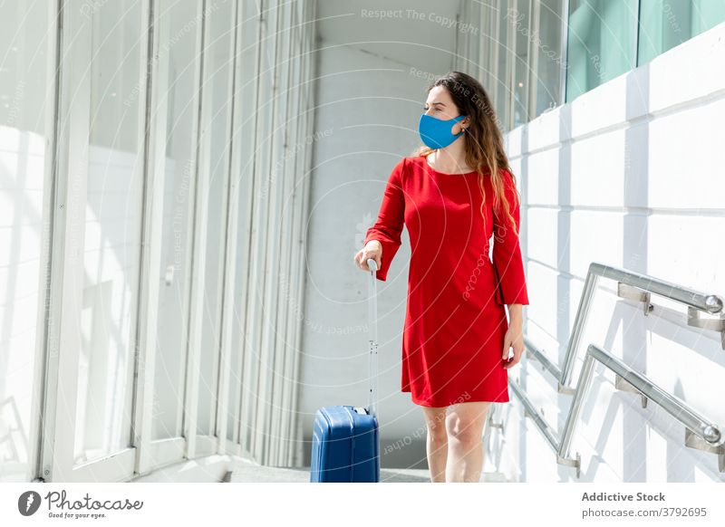 Traveling woman with baggage in airport travel wait flight departure suitcase mask coronavirus female tourist passenger vacation holiday window trip journey