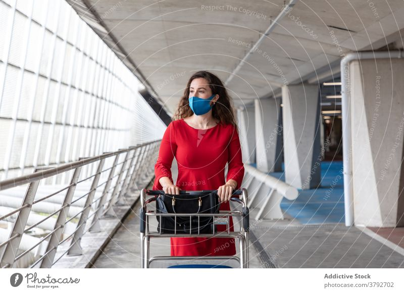 Woman with luggage trolley in airport woman travel baggage departure walk tourist female journey trip destination holiday wait vacation tourism flight passenger