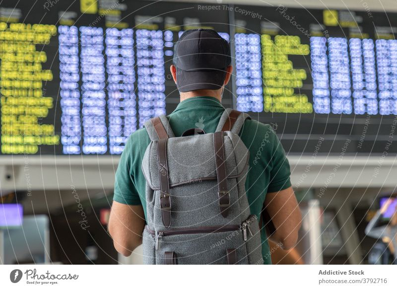 Unrecognizable man with backpack in airport departure board schedule traveler check wait flight tourist male international vacation trip passenger modern
