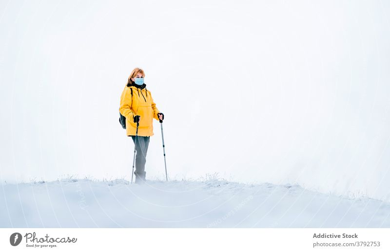 Active traveler in warm wear and medical mask in snowy mountains hiker trekking covid19 coronavirus active adventure female covid 19 pandemic freedom nature