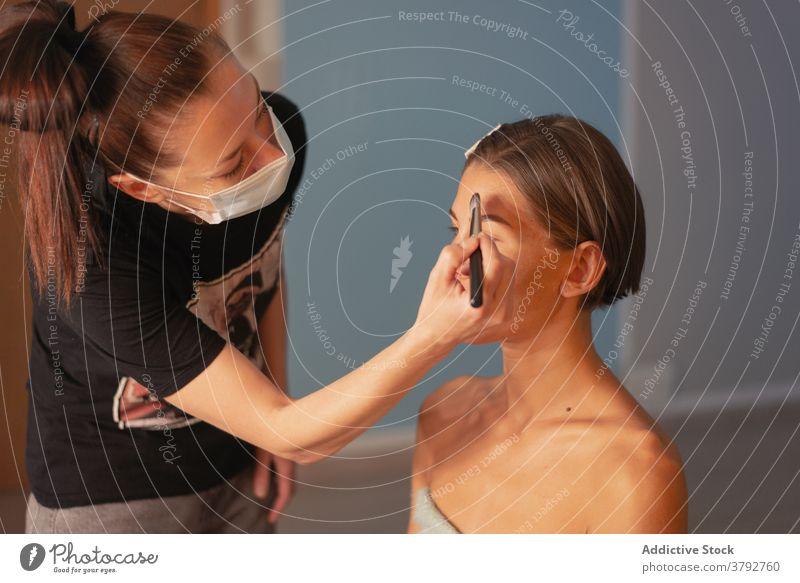 Visagiste doing makeup on face of model artist foundation salon cosmetic charming prepare visage women brush care style fashion beauty glamour creative