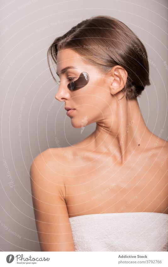 Serene woman doing daily routine treatment in studio eye patch skin care beauty black patch female natural cosmetology wellness perfect charming smooth