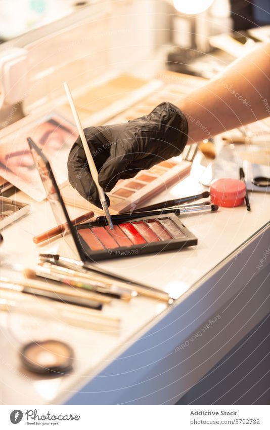 Crop makeup artist applying cosmetic product visage visagiste lipstick palette professional glove latex protect table bright beauty salon liquid brush glamour