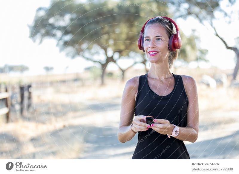 Woman using MP3 player and headphones in park woman gadget listen mp3 sound melody audio podcast music entertain song young concentrate focus headset modern