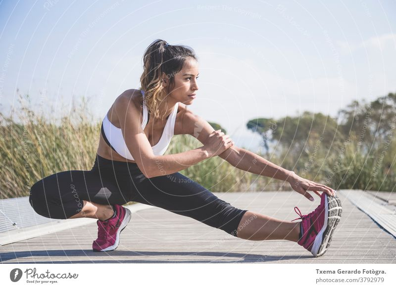Attractive woman doing stretching exercises outdoors activewear athletic girl running cardio fitness jogging lifestyle sport sportwear park lake sun jumping