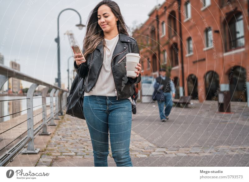 Young woman using her phone. street smartphone city mobile people urban cellphone female text young sms message outdoor adult online internet use lifestyle
