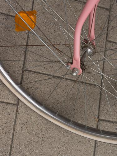 Detail of a bicycle front wheel with pink fork and orange reflector Bicycle Front wheel Fork Pink Reflector Bird's-eye view Orange concrete paving Old