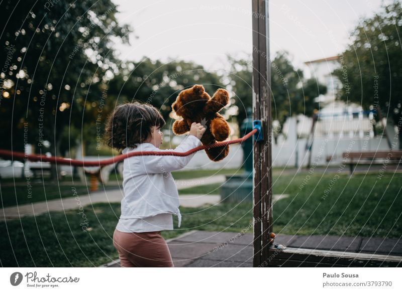 Little girl playing with Teddy bear at playground Playground Park Child childhood Bear Toys Cute Joy kid Small Infancy Playing Brown Colour photo Exterior shot