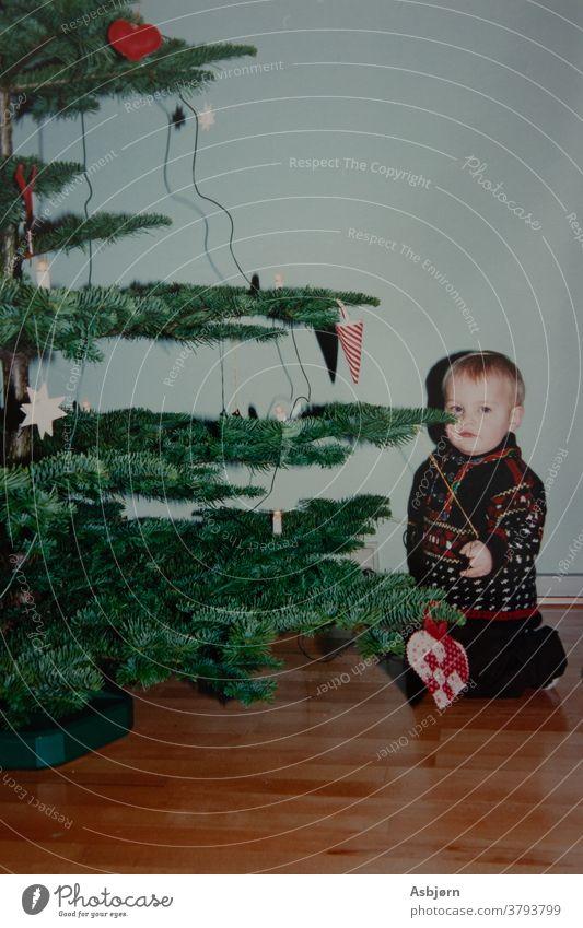 Boy by Christmas tree Film boy kid Christmas & Advent Christmas decoration Christmas tree decorations Colour photo sitting old retro Scan retro style