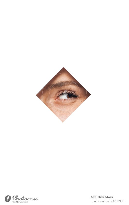 Anonymous woman looking through hole in wall eye frame spy peek curious peep makeup beauty brown eyes female square shape fashion design concept facial cosmetic