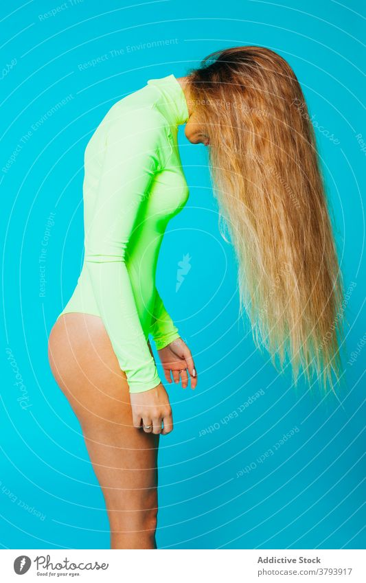 Long haired blonde woman in bodysuit fashion long hair flying hair style outfit beauty color vibrant young fair hair female model bright colorful vivid slim