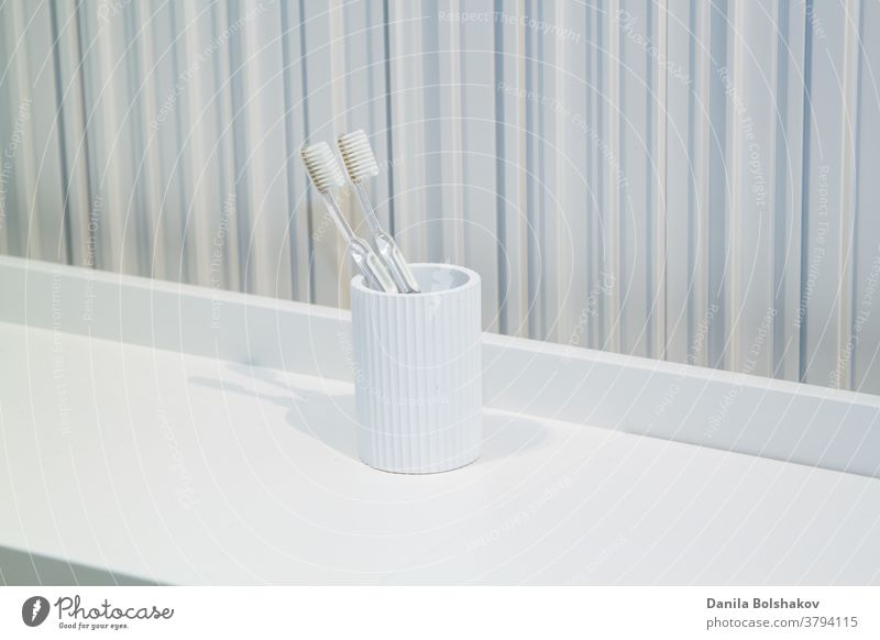 two toothbrushes in white white cup in bathroom on striped background dental equipment daily toothbrush holder caries routine luxury clinic protection