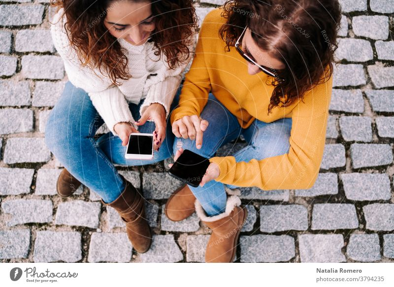 Selective focus. Two beautiful women sitting on the street and using their phones. They are both looking at something on the cell. Technology lifestyle