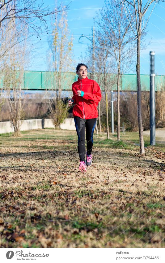 Front view of a fitness girl training running in the morning park exercise jogging woman nature runner jogger lifestyle 1 sport person autumn female active wear