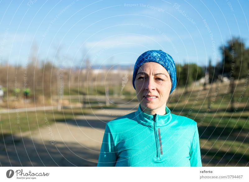 Portrait of mature runner woman with sport headband in the park fit nature old female aged lifestyle person training senior outdoors healthy elderly athletic