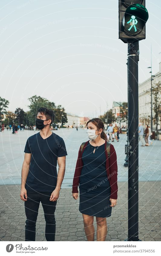 Man and woman waiting at pedestrian crossing next to traffic lights wearing the face masks to avoid virus infection and to prevent the spread of disease in time of coronavirus