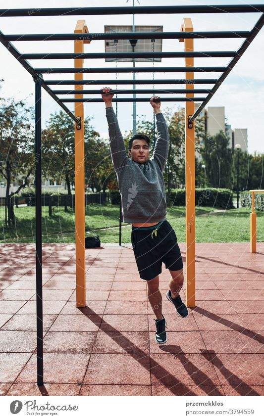 Young man bodybuilder exercising on monkey bars during his workout in a modern calisthenics park care caucasian health lifestyle male one outdoors person sport