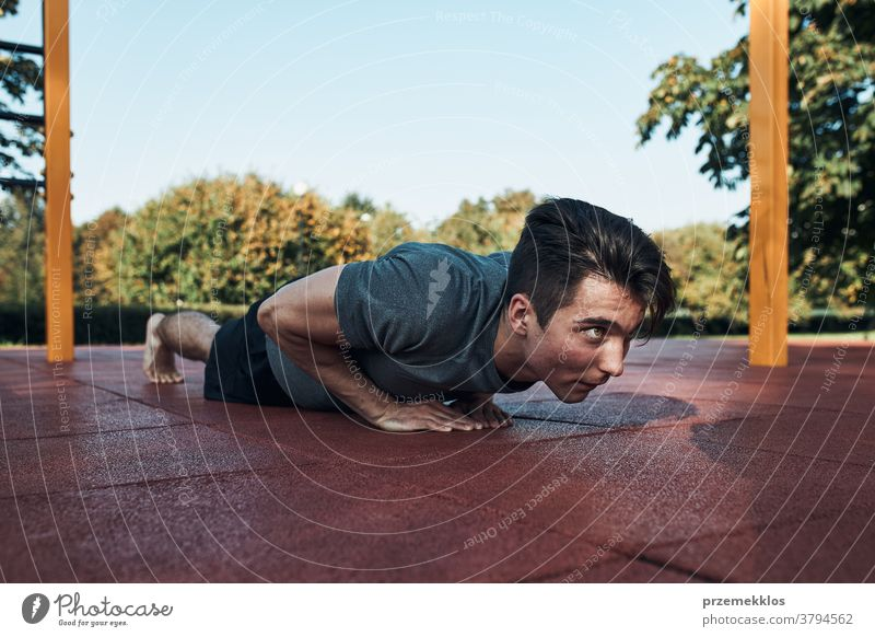 Young man doing push-ups on a red rubber ground during his workout in a modern calisthenics street workout park care caucasian health lifestyle male one