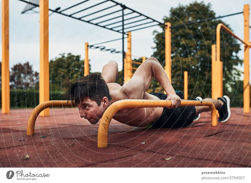 Young shirtless man bodybuilder doing push-ups on a parallel bars during his workout in a modern calisthenics park care caucasian health lifestyle male one