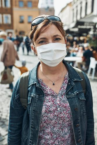 Young woman standing in a street downtown looking at camera wearing the face mask to avoid virus infection care caucasian contagious corona coronavirus cover