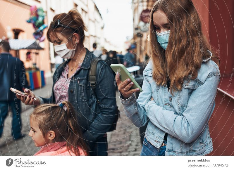 Young women using smartphones standing in a street downtown wearing the face masks to avoid virus infection call care caucasian chat contagious corona