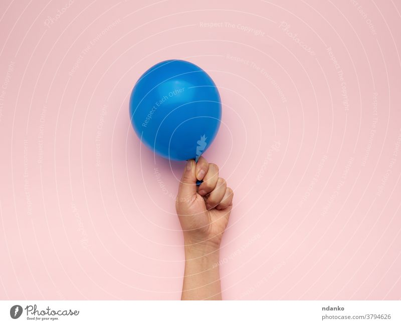 female hand holding an inflated blue air balloon anniversary arm background ballon birthday blank caucasian celebration closeup decoration festive filled float