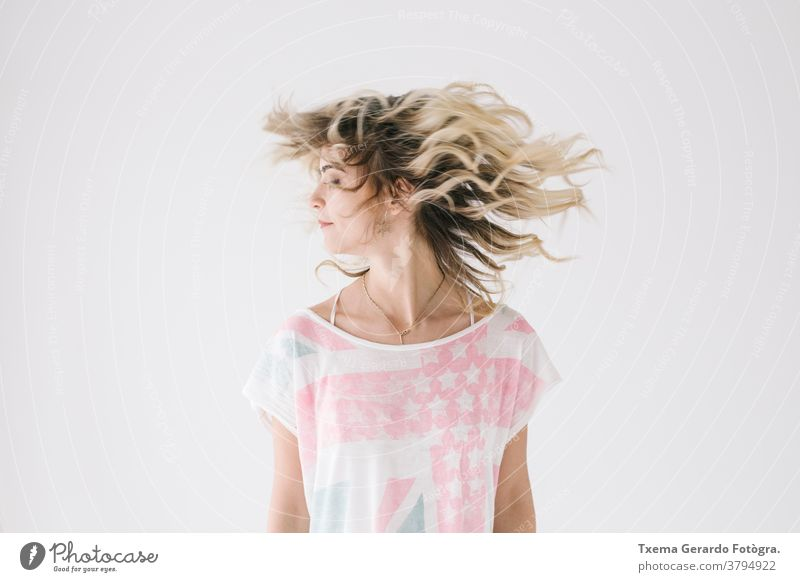 Natural portrait of blonde girl shaking her hair on white background natural motion shake shirt unfiltered expression european caucasian woman young adult