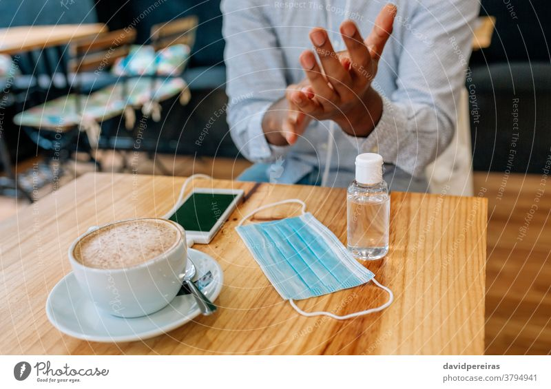 Unrecognizable man disinfecting his hands with hydroalcoholic gel disinfecting hands coronavirus hand rub rubbing applying mask on table coffee shop