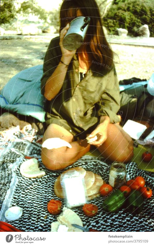 woman sitting on the ground with a picnic Picnic picnic blanket drinking globetrotter traveling camping simple simple living outside outdoor outdoors trip food